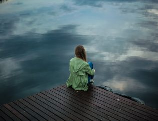 photo of a girl sitting alone on dock
