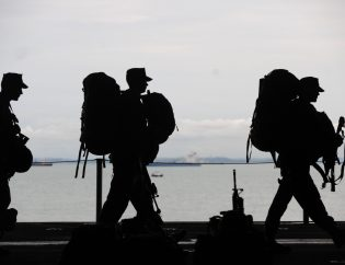 Silhouette of Military Personnel Walking On Ship