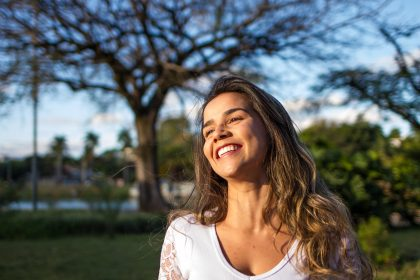 Woman in white smiling outside