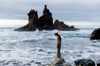 Woman alone on rock at the beach
